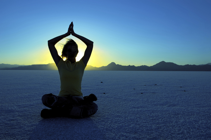 silhouette of a woman meditating on a beach at sunset