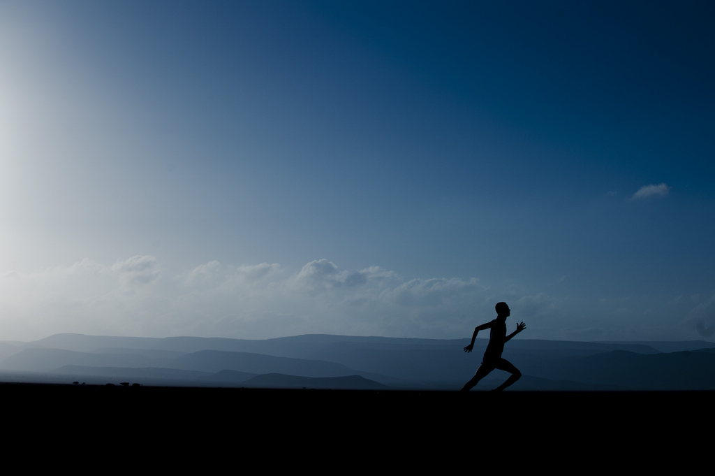 Silhouette of person running at dusk