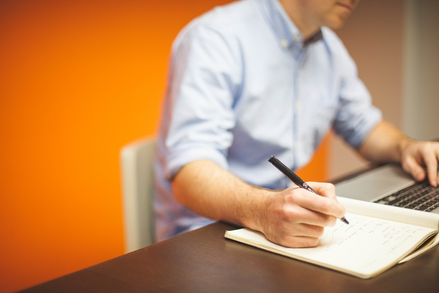 man sitting a desk with notebook
