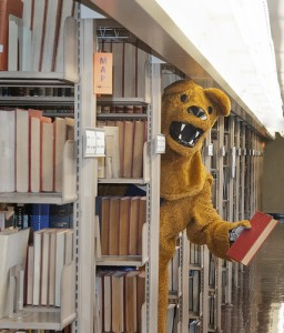 Nittany Lion mascot standing in Penn State library stacks holding book