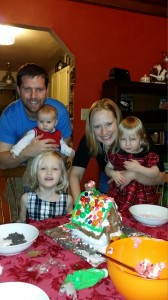 Megan Baril decorating a gingerbread house with her family