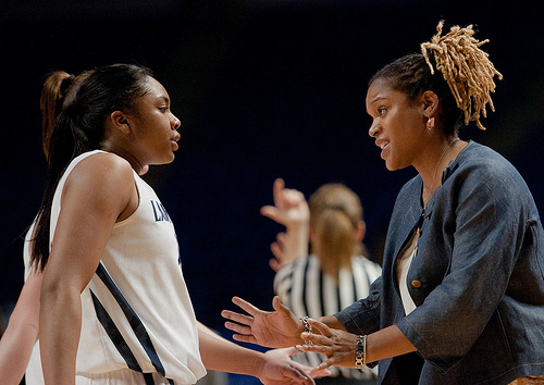 Coach Coquese Washington speaks with Lady Lion player, Alex Bentley, during a short time-out.