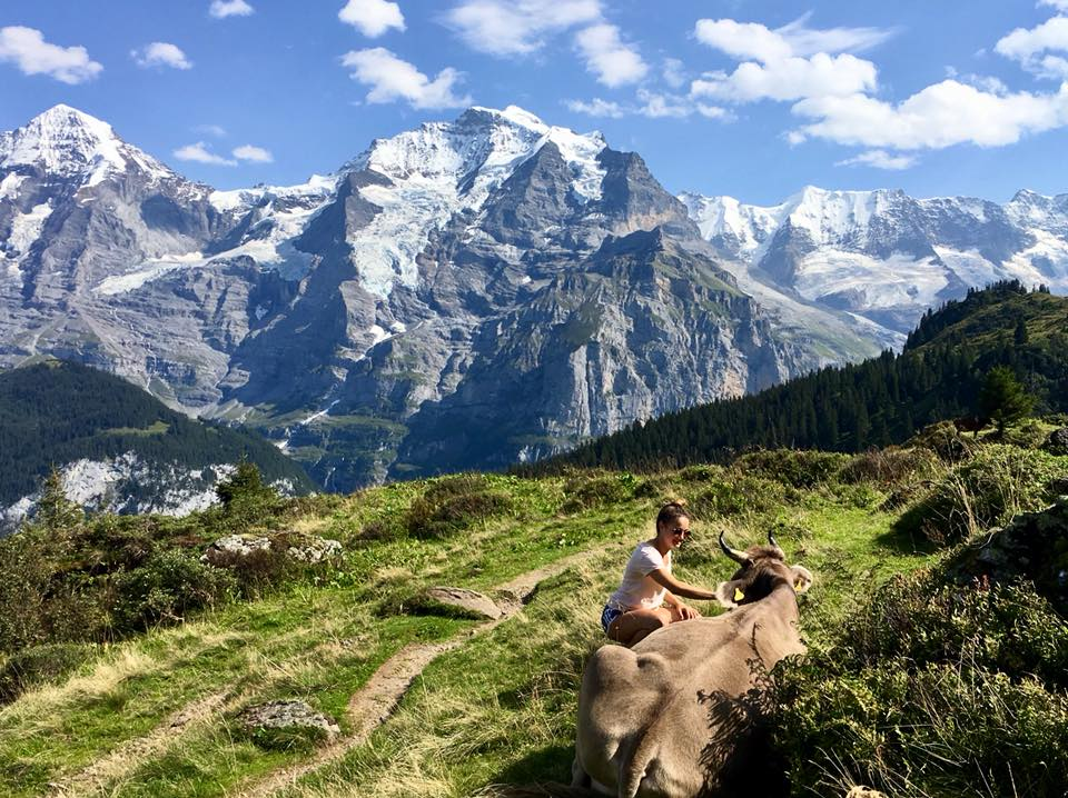 Kasey Altman and cow outdoors in Switzerland