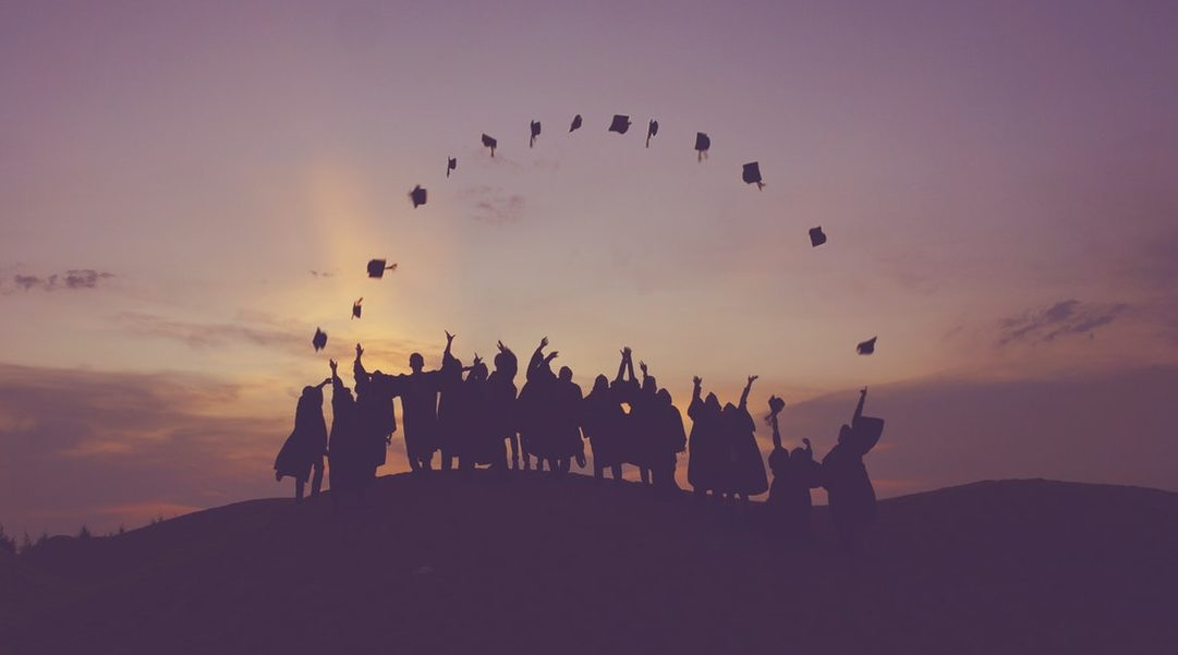 Graduates throw their caps into the air in the sunset