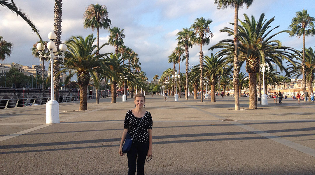 Kate, Penn State World Campus graduate assistant, stands on a street lined with palm trees